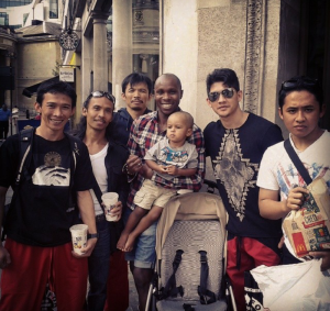 A random black man and drags his innocent child into an unprovoked photo-bombing with the cast of The Raid!